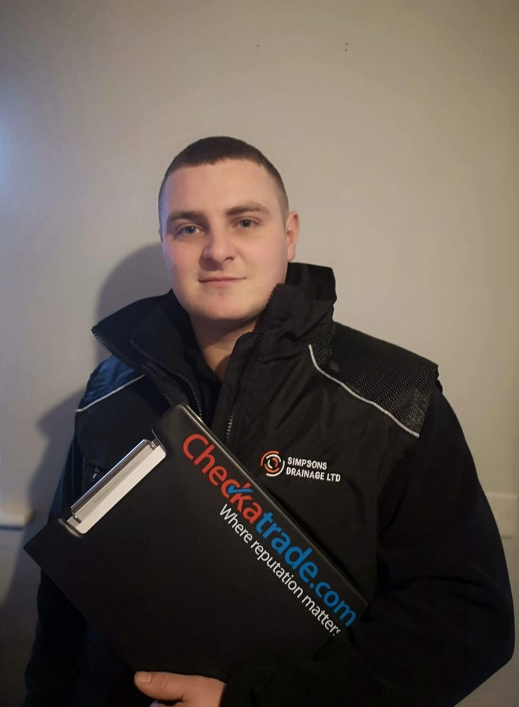 Person in Simpsons Drainage Ltd uniform, holding check a trade clipboard. Simpsons Drainage, Drain clearance, drain unblocking, septic tank services, septic tank emptying, drain camera surveys, drain repairs, drain lining, new drains in Warminster, Frome, Trowbridge.