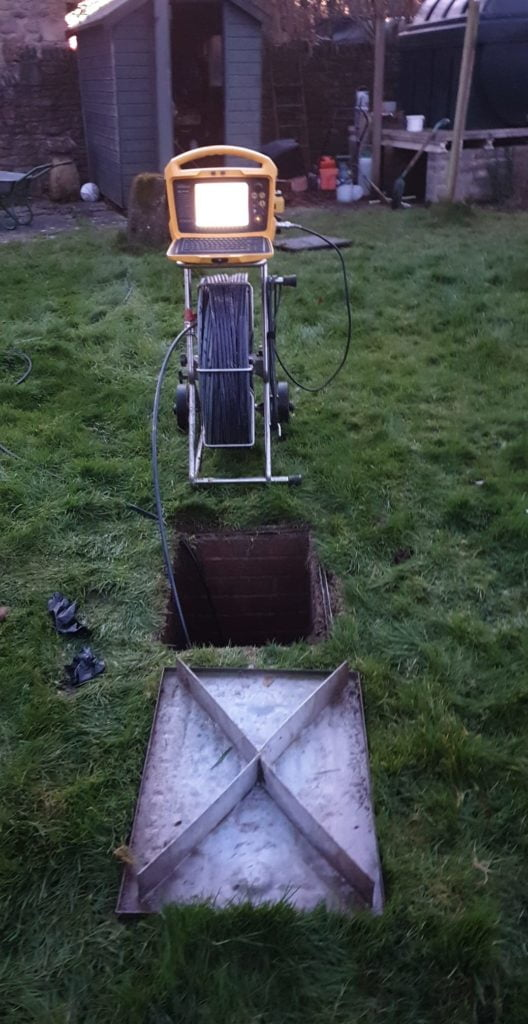 Open drain with survey rod inside. Residential Drainage. Simpsons Drainage, Drain clearance, drain unblocking, septic tank services, septic tank emptying, drain camera surveys, drain repairs, drain lining, new drains in Warminster, Frome, Trowbridge.