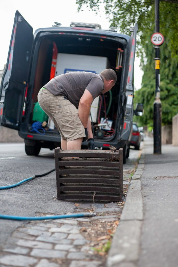 Person wearing Simpsons Drainage Ltd uniform in front of company van. Simpsons Drainage, Drain clearance, drain unblocking, septic tank services, septic tank emptying, drain camera surveys, drain repairs, drain lining, new drains in Warminster, Frome, Trowbridge.