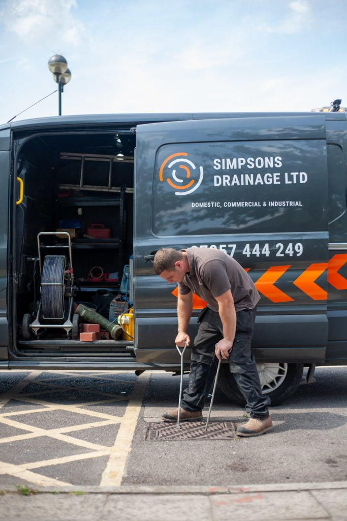 Person lifting manhole cover from drain. Simpsons Drainage, Drain clearance, drain unblocking, septic tank services, septic tank emptying, drain camera surveys, drain repairs, drain lining, new drains in Warminster, Frome, Trowbridge.