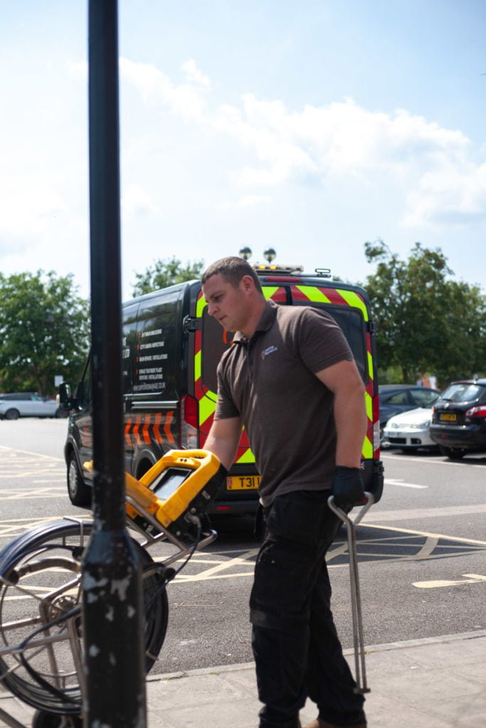 Person carrying drain surveying equipment. Simpsons Drainage, Drain clearance, drain unblocking, septic tank services, septic tank emptying, drain camera surveys, drain repairs, drain lining, new drains in Warminster, Frome, Trowbridge.
