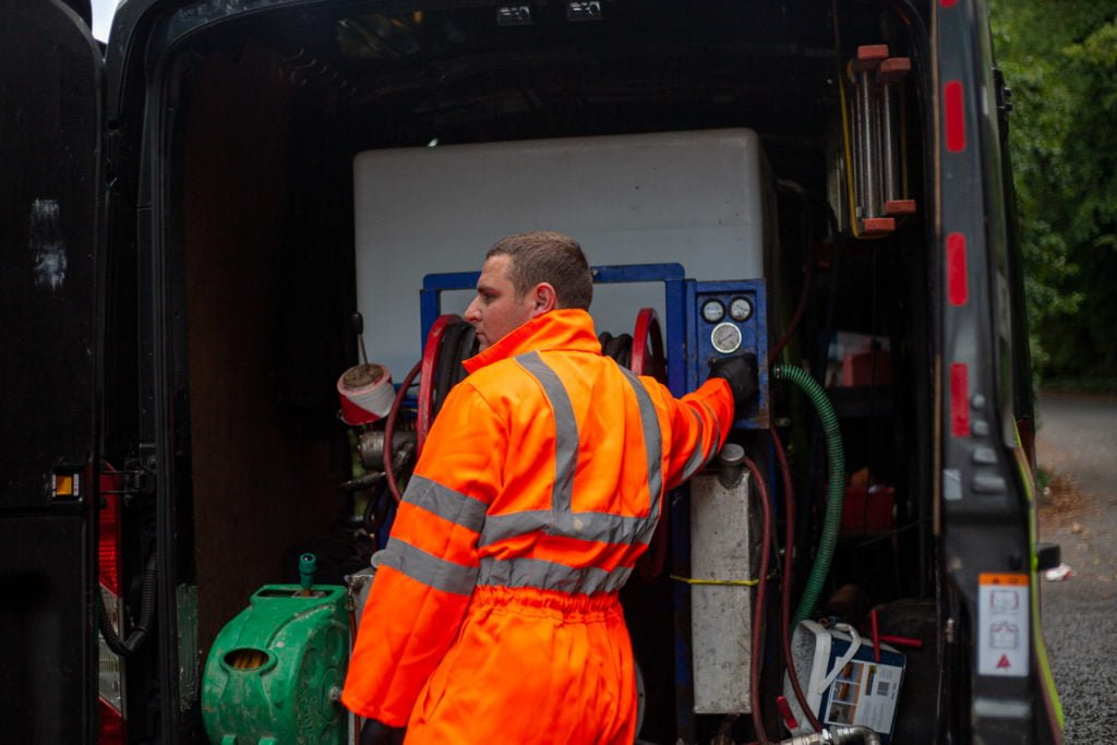 Person wearing high visibility outfit using drain equipment in company van. Simpsons Drainage, Drain clearance, drain unblocking, septic tank services, septic tank emptying, drain camera surveys, drain repairs, drain lining, new drains in Warminster, Frome, Trowbridge.