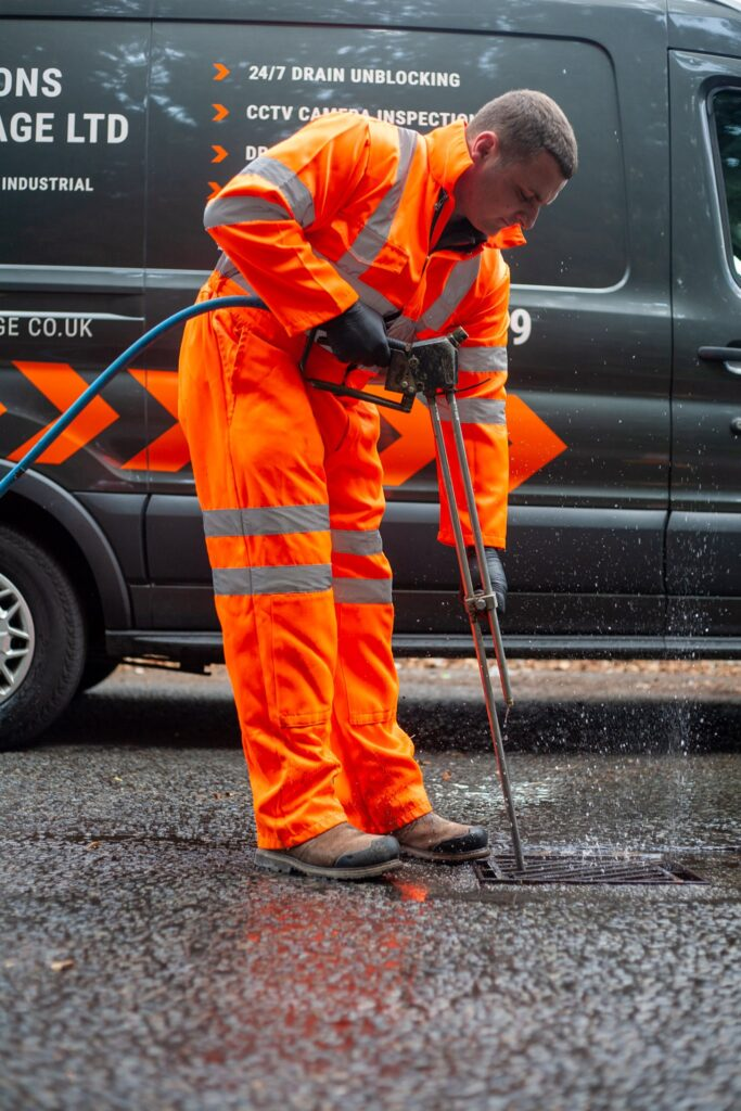 Person in high visibility outfit unblocking drain, in front of company van. Simpsons Drainage, Drain clearance, drain unblocking, septic tank services, septic tank emptying, drain camera surveys, drain repairs, drain lining, new drains in Warminster, Frome, Trowbridge.