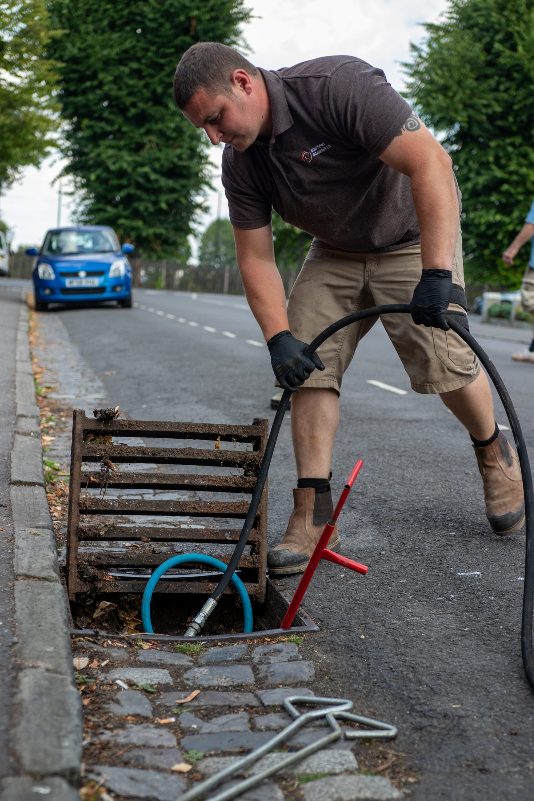 Person carrying out drain unblocking on road. Simpsons Drainage, Drain clearance, drain unblocking, septic tank services, septic tank emptying, drain camera surveys, drain repairs, drain lining, new drains in Warminster, Frome, Trowbridge.